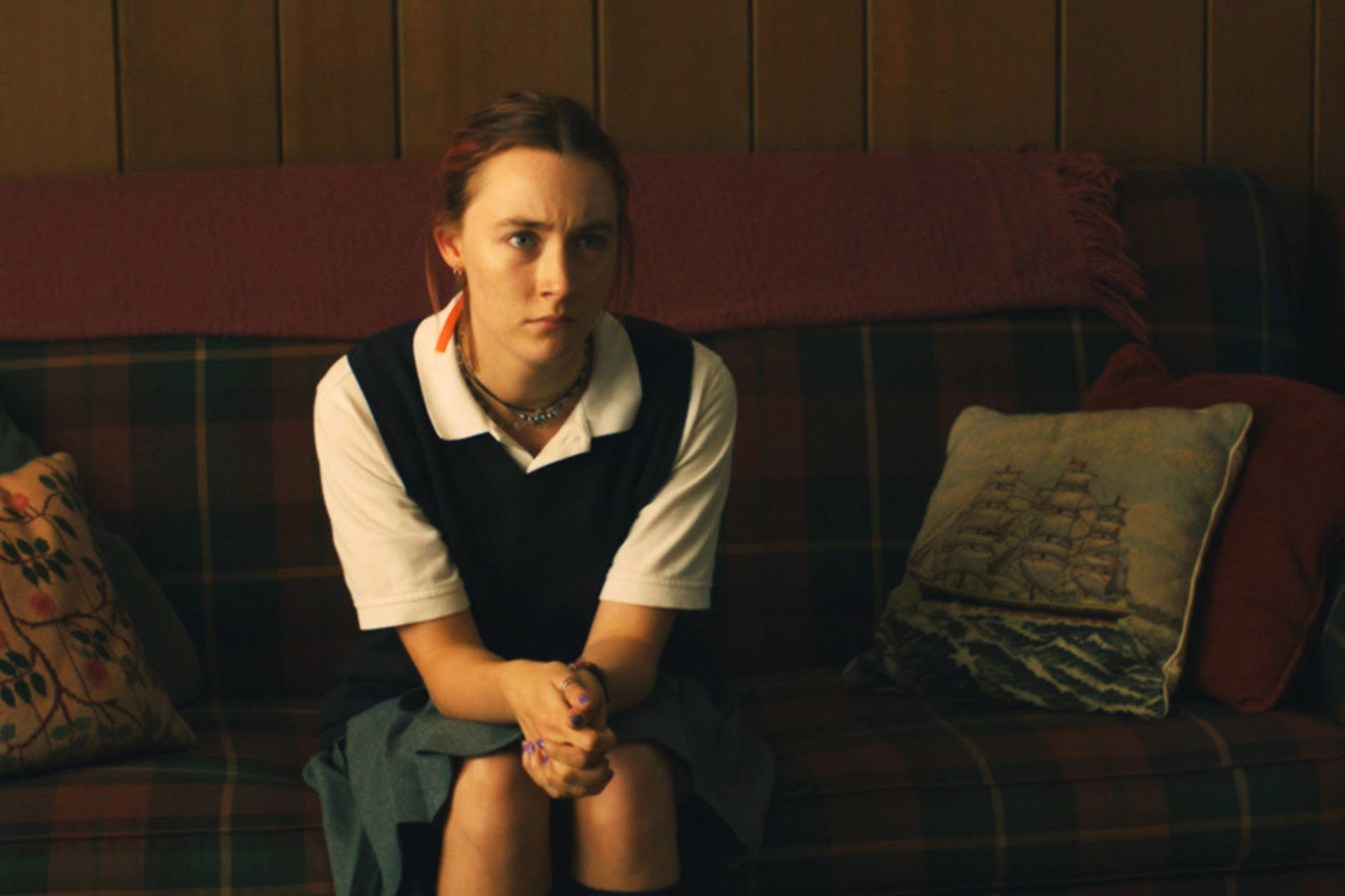 """Christina sitting on a couch in her school uniform on """"Lady Bird"""""""