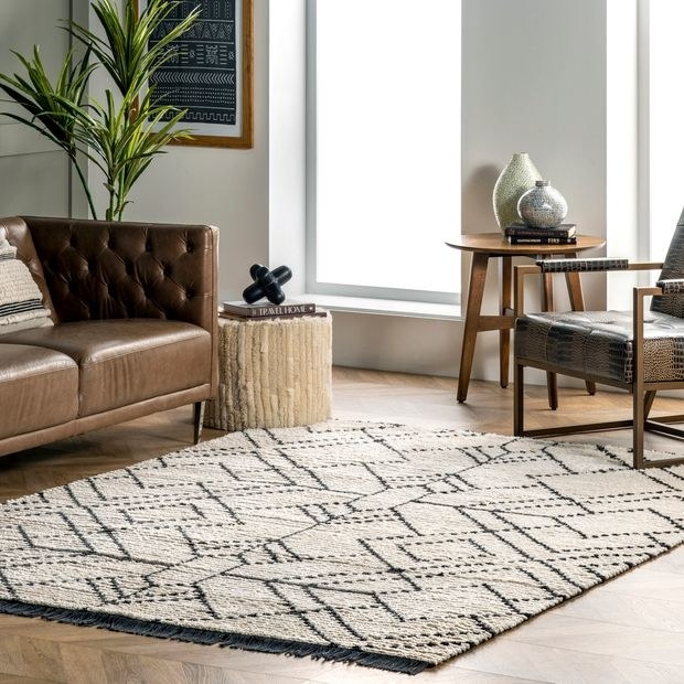 tassel black and white rectangle area rug next to brown couch and chairs