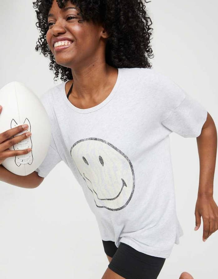 Woman carrying football in white smiley face shirt