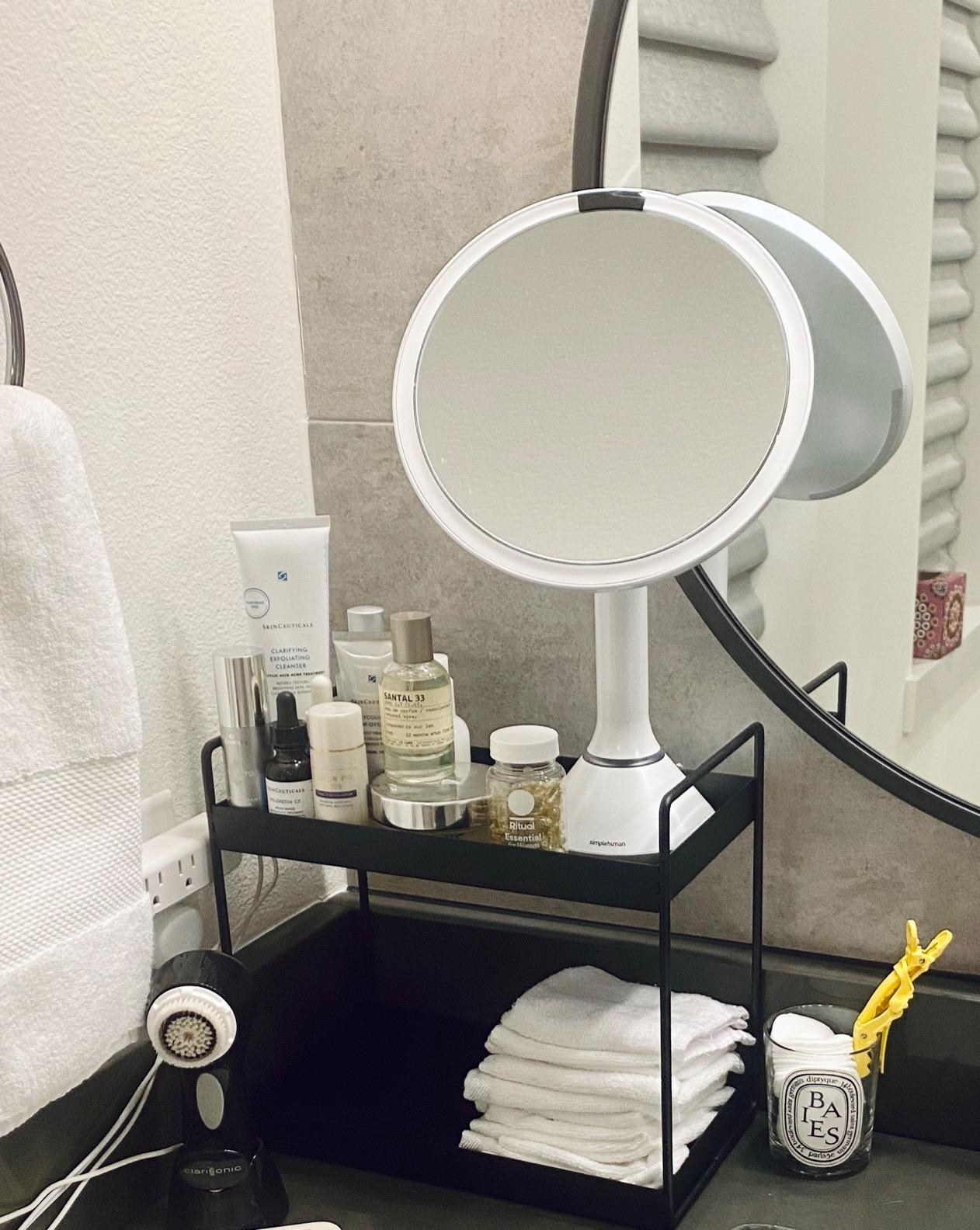 reviewer image of the two-tier black shelves on a bathroom counter
