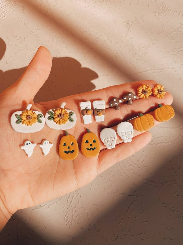 palm holding stud earrings of fall-centric things like pumpkins and ghosts
