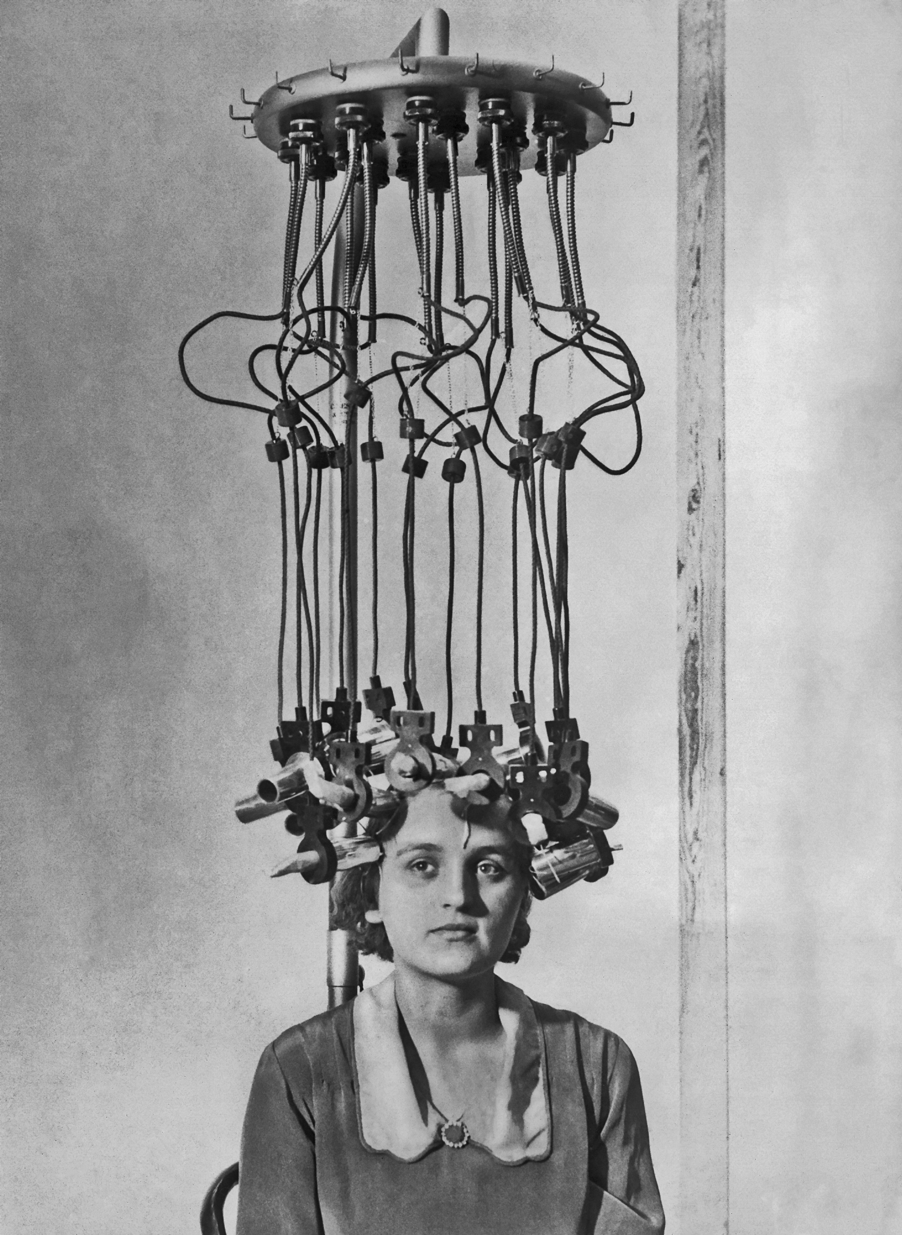 A model having her hair permed by a permanent wave machine