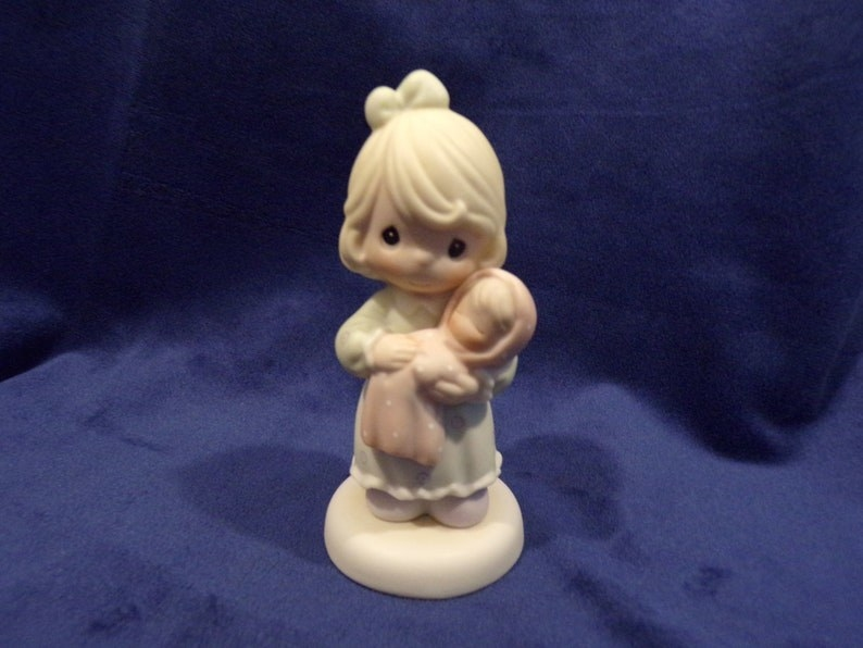Figure of a blonde little girl carrying a baby doll