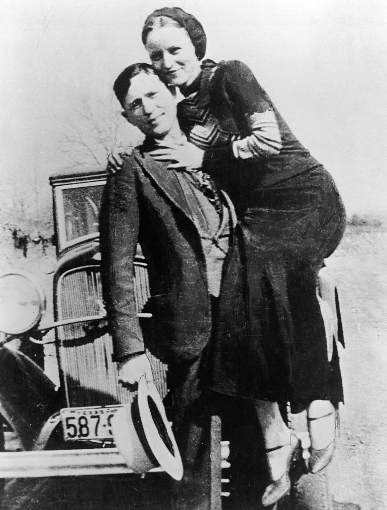 Clyde Barrow posing for a photo with Bonnie Parker in front of their car