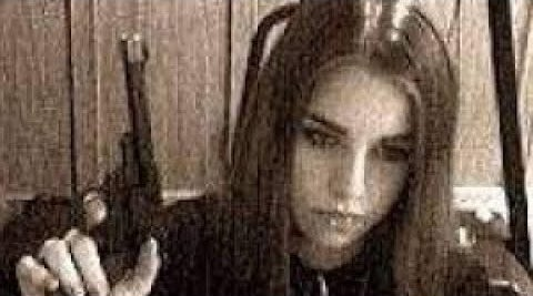 A blurry image of Jasmine Richardson holding a gun
