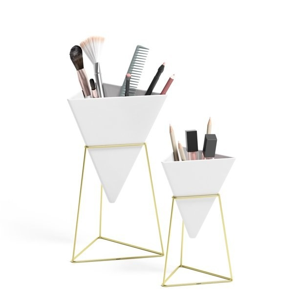 Two gold and white vases with makeup