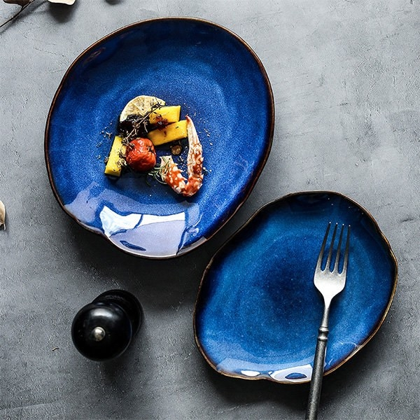 Two of the uniquely shaped blue plates on a table