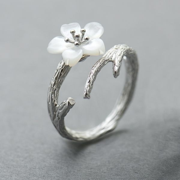 The silver ring with an open design and a white cherry blossom
