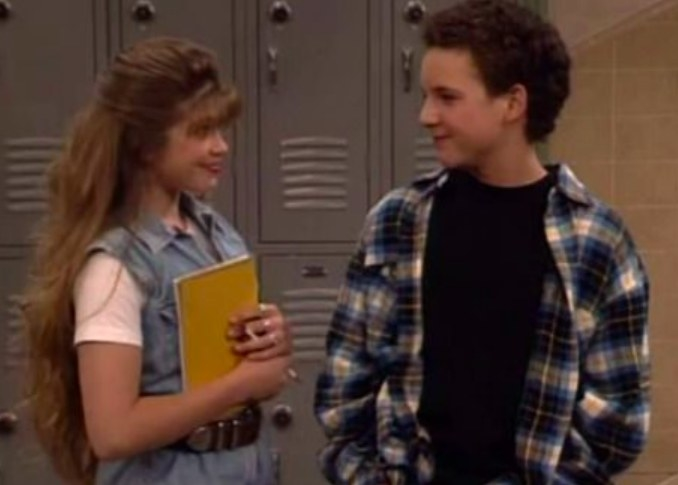 Topanga and Corey stand in front of lockers smiling at each other