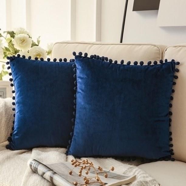 two blue tassled velvet pillows