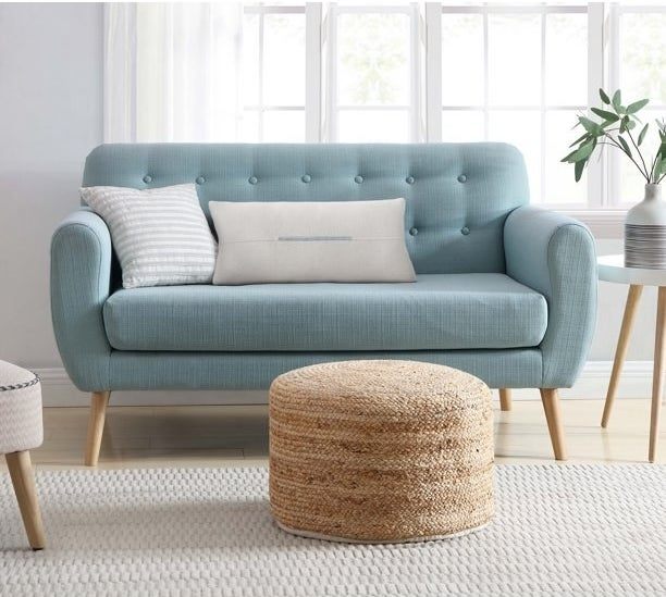 natural jute floor pouf next to a blue couch