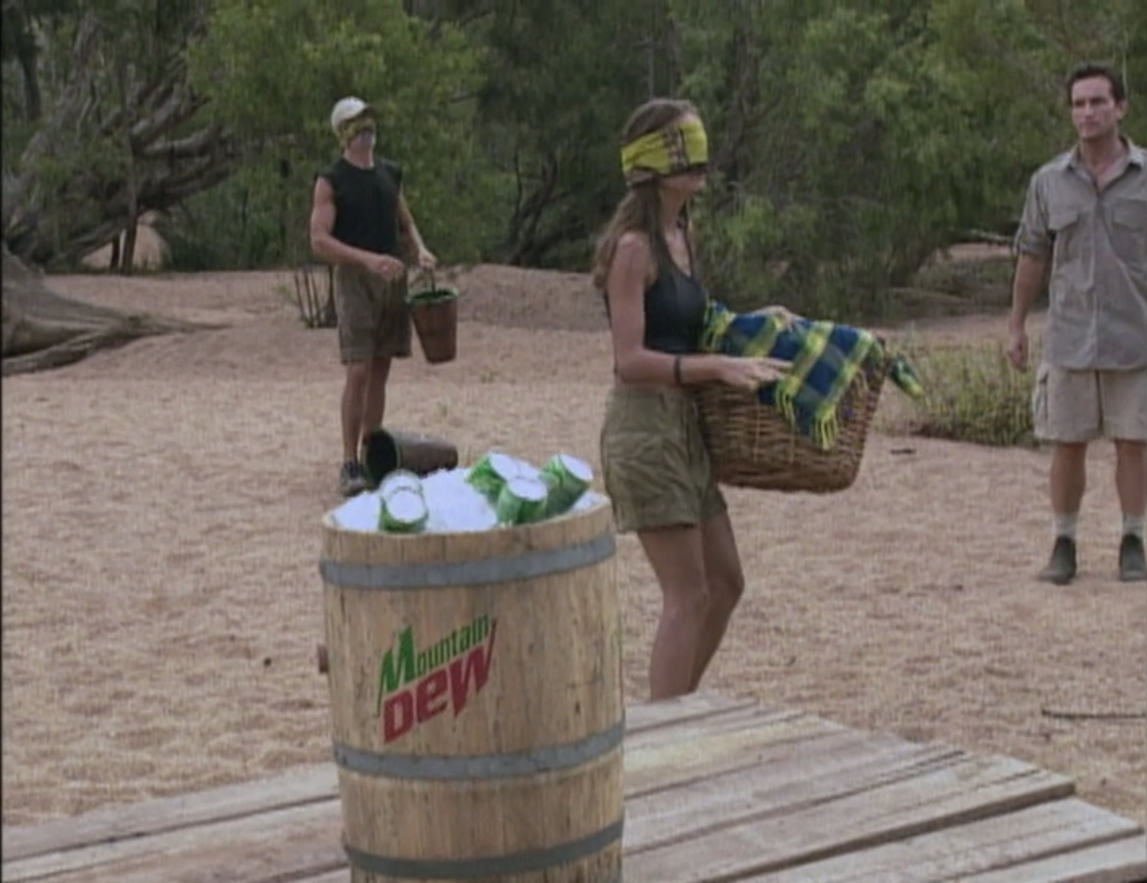 Jeff Probst watches blindfolded castaways carry basket near a barrel of Mountain Dew