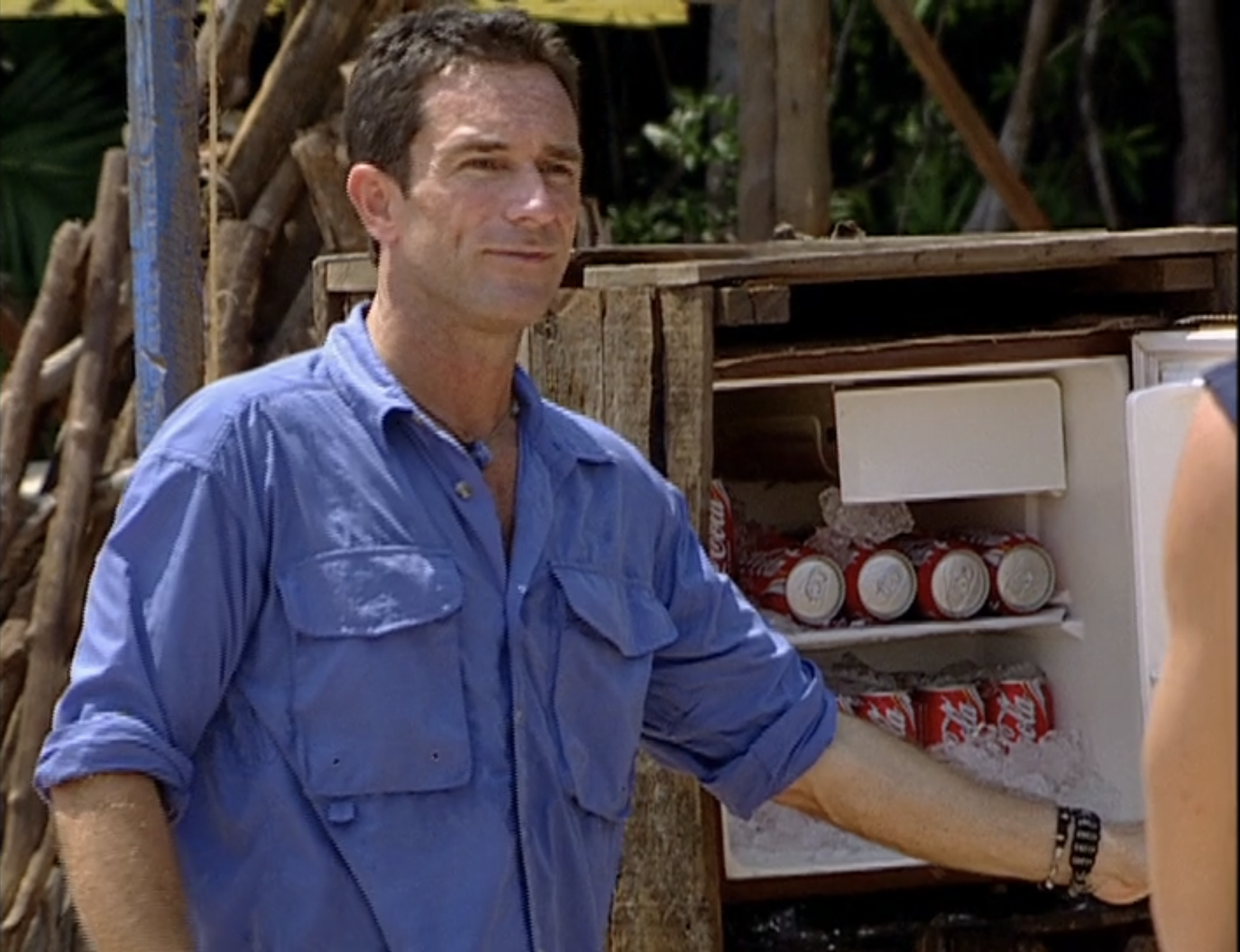 Jeff Probst stands next to a wodden fridge filled with Coke