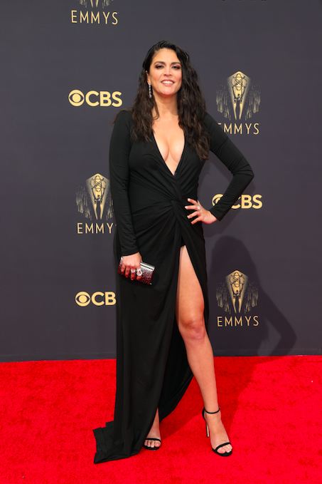 Cecily Strong on the red carpet in a low cut, long sleeve black gown with a high slit