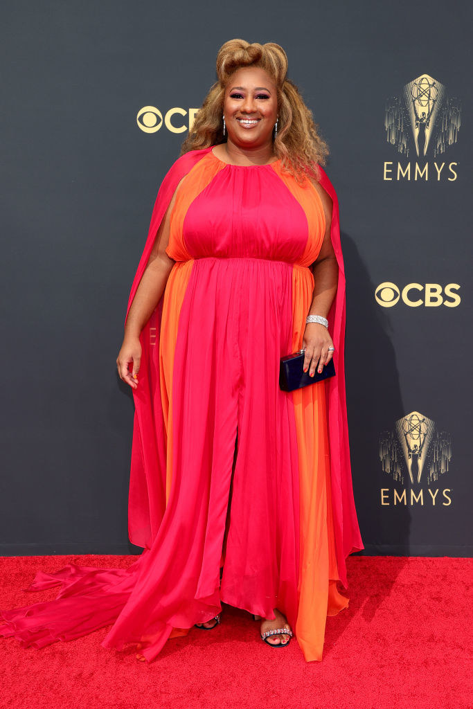 Ashley Nicole Black on the red carpet in a red and orange gown