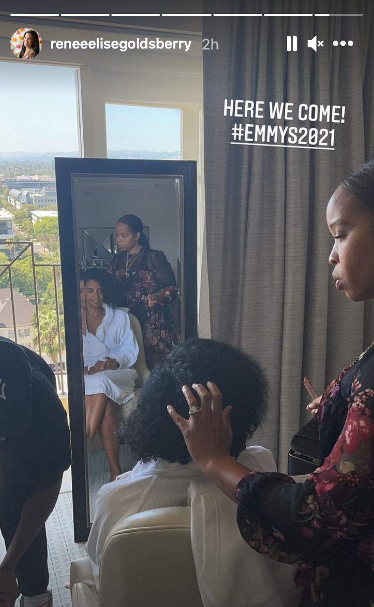 Renee Elise Goldsberry sits in a chair in front of a full length mirror getting her hair done