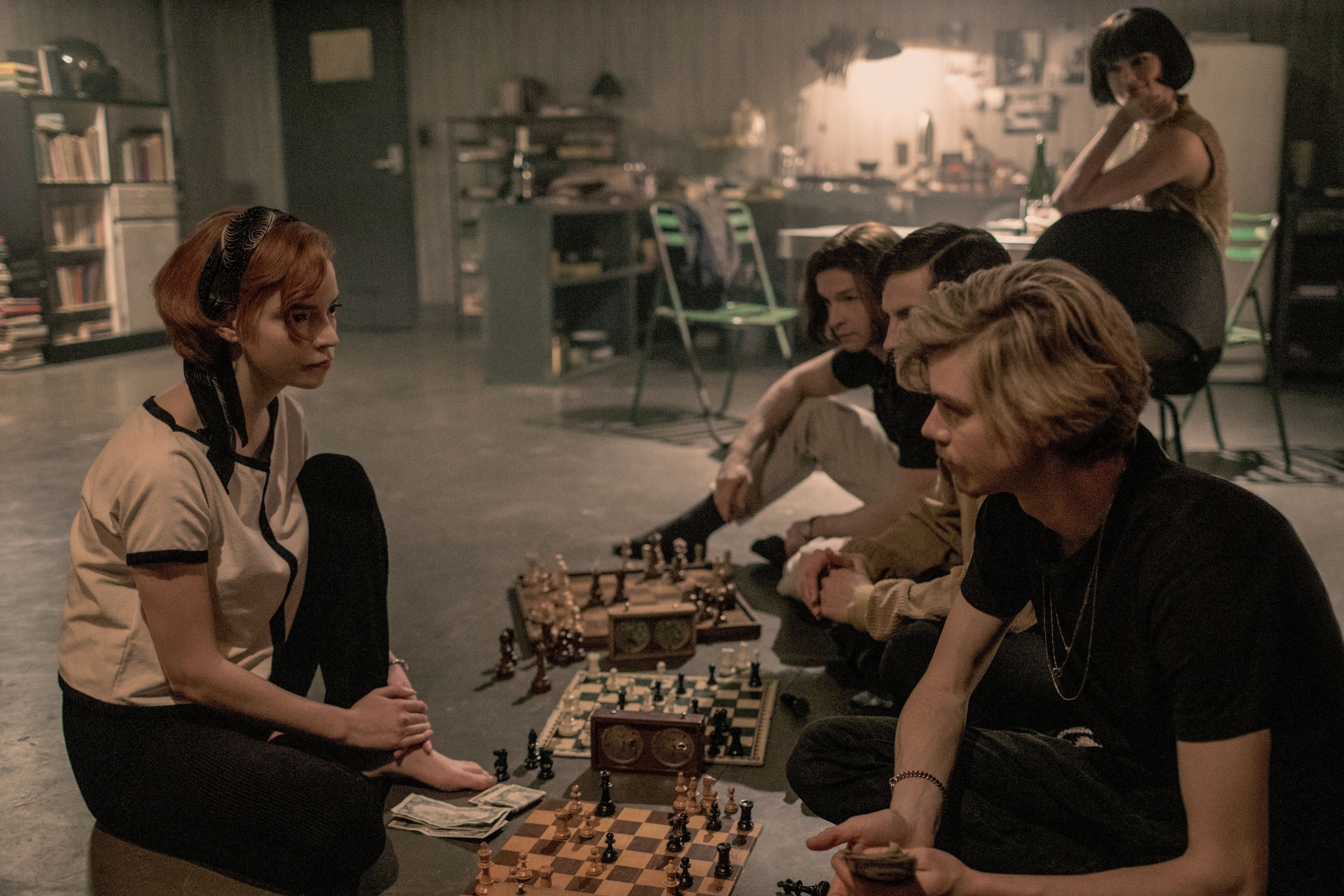 Anya sitting on the floor playing chess with several others