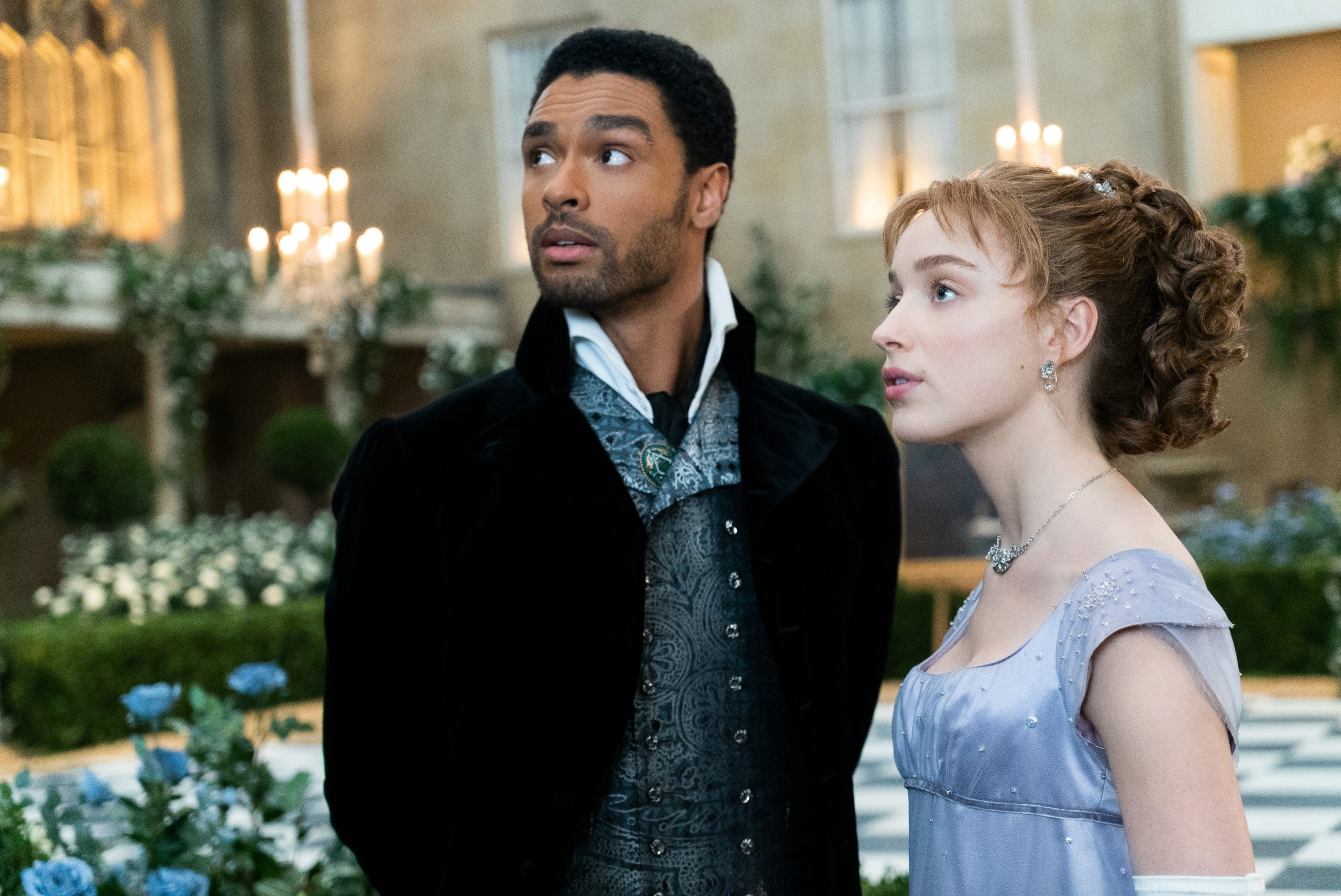 Regé-Jean Page and Phoebe Dynevor standing next to each at a ball in a scene from Bridgerton
