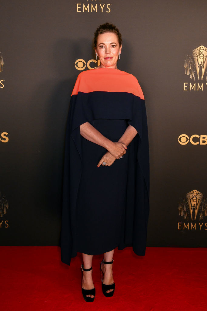 Olivia Colman on the red carpet in a navy and orange dress