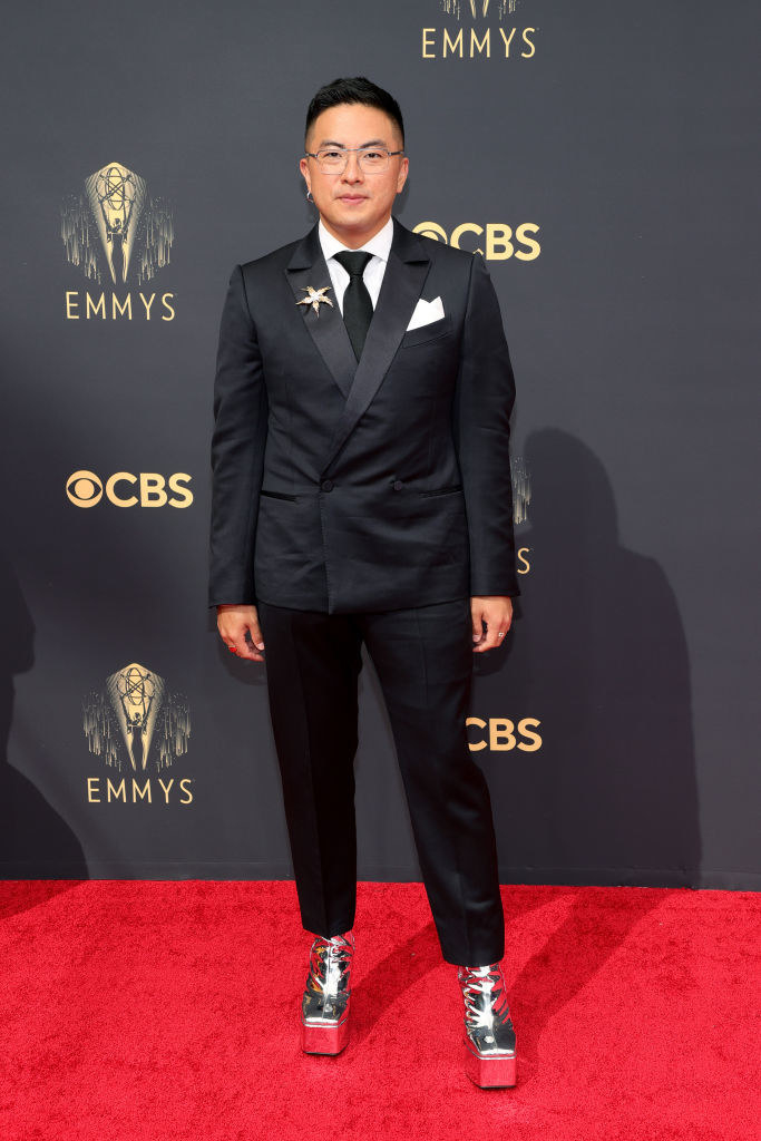 Bowen Yang on the red carpet in a black suit and silver platform heels
