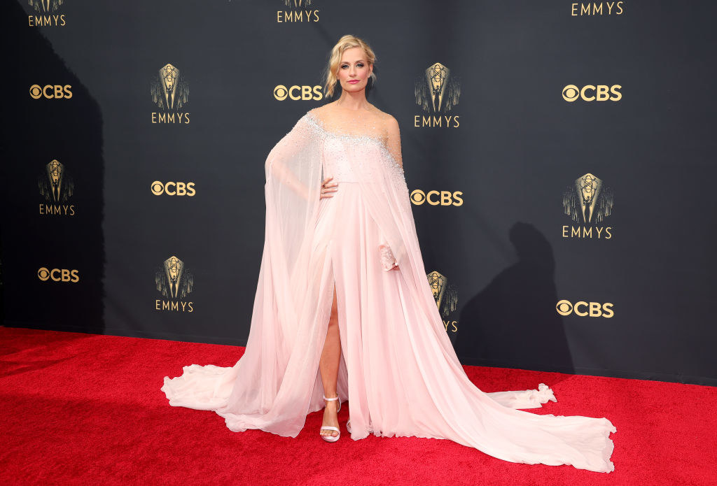 Beth Behrs on the red carpet in a flowing pink gown with a high slit