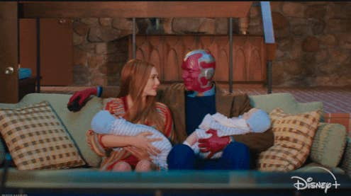 Wanda and Vision sitting on their living room couch and holding their twin boys