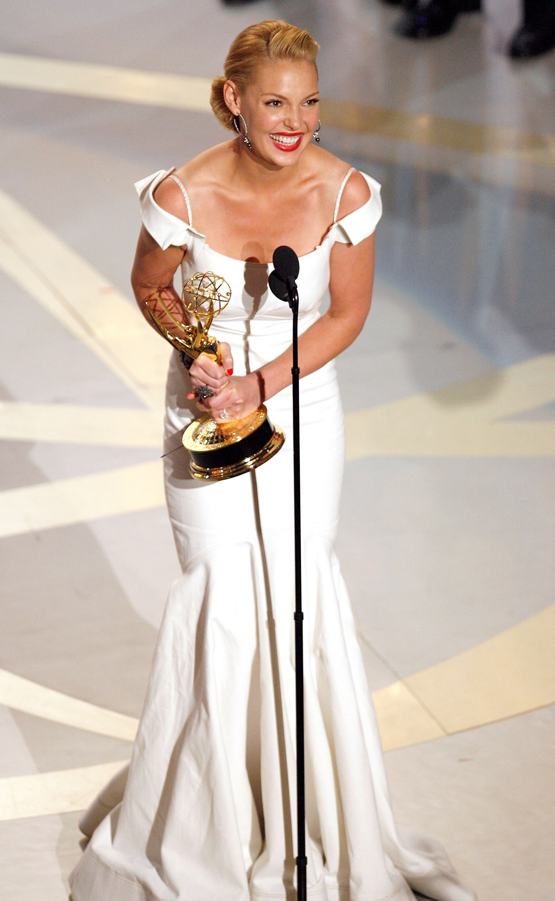 Heigl leans into a microphone while clutching an Emmy in her hands