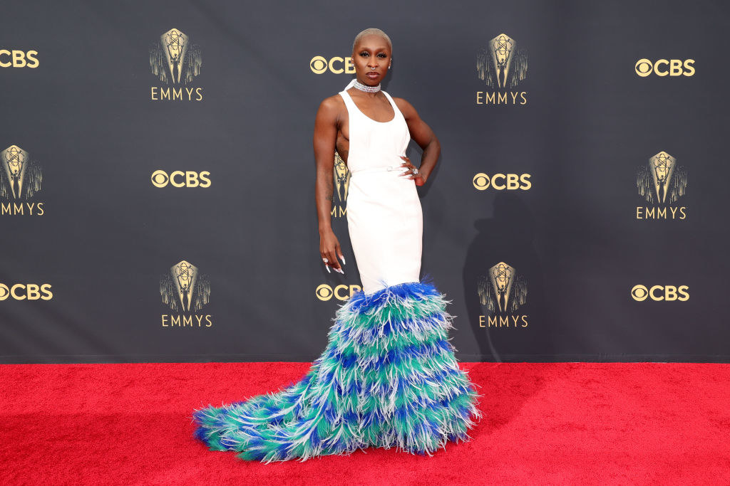 Cynthia Erivo on the red carpet in a white gown with a blue feathered bottom