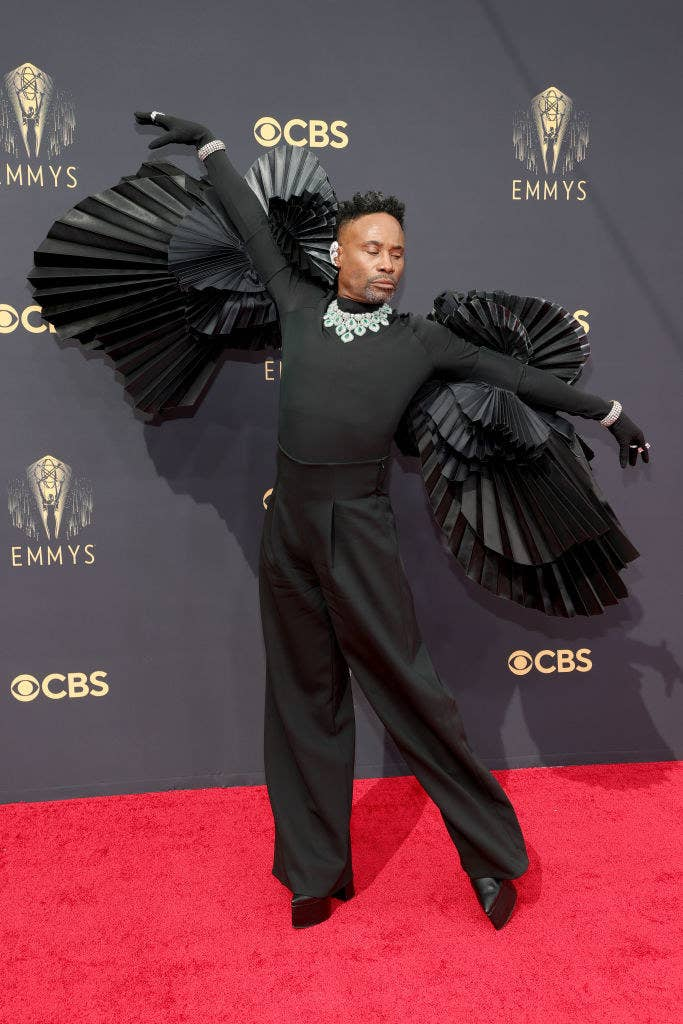 Billy Porter with his arms outstretched to show off the ruffled sleeves