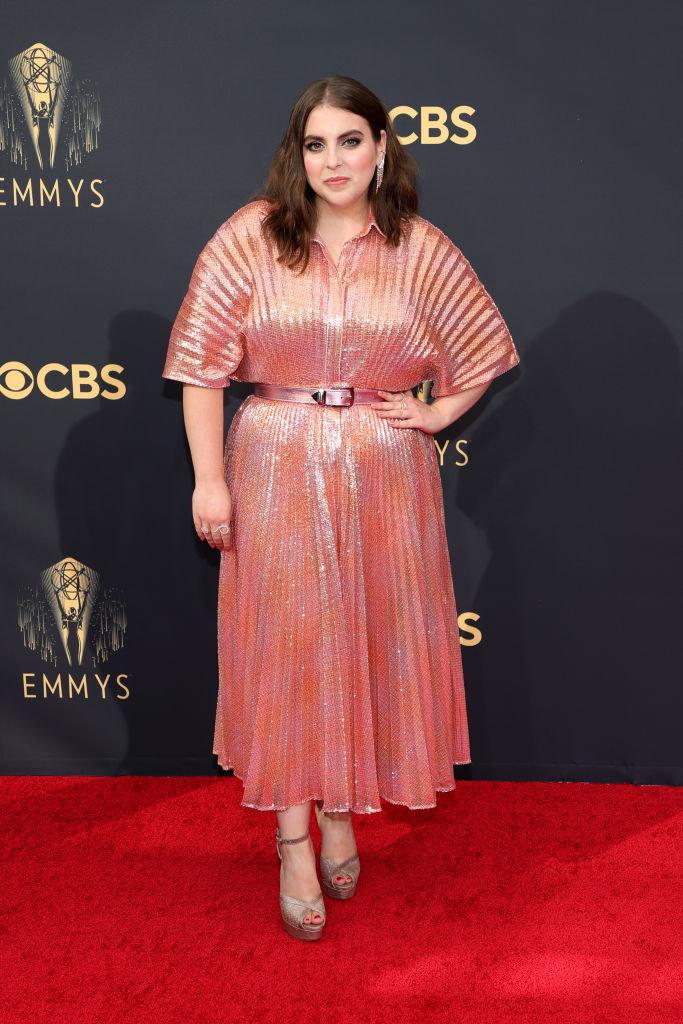 Beanie Feldstein on the red carpet in a calf-length coral dress