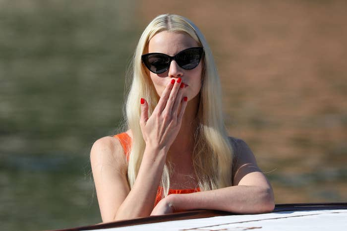 Anya about to blow a kiss while standing on a boat