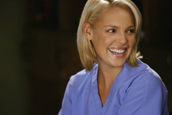 Katherine Heigl smiles in a direction off camera while wearing scrubs