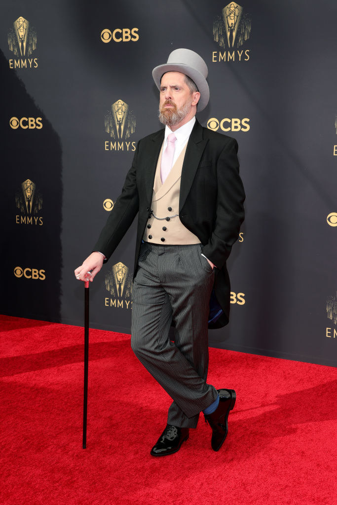 Brendan Hunt on the red carpet in a classic suit, top hat, cane, and tails