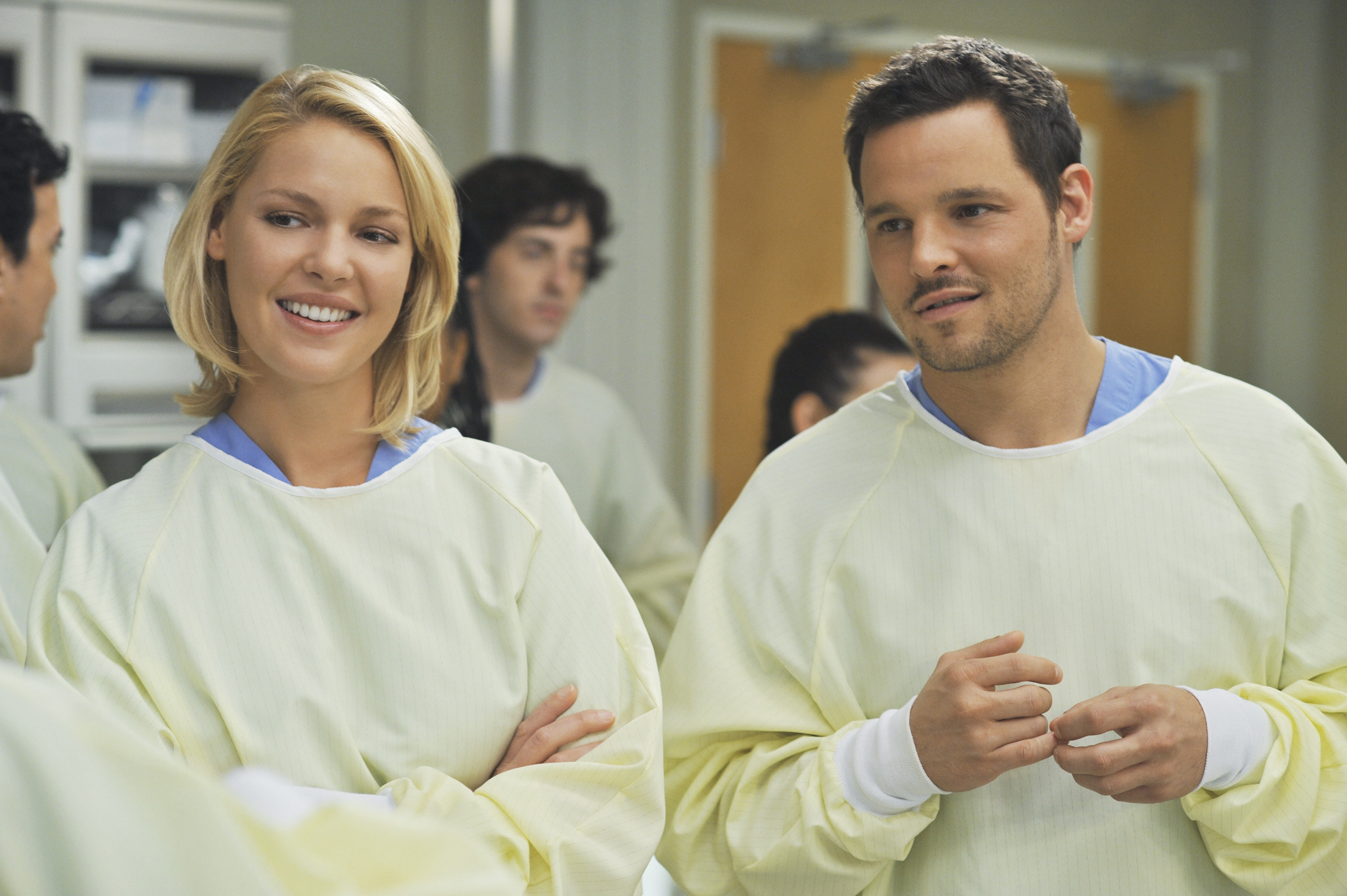Heigl stands with her arms crossed next to another actor while wearing OR scrubs