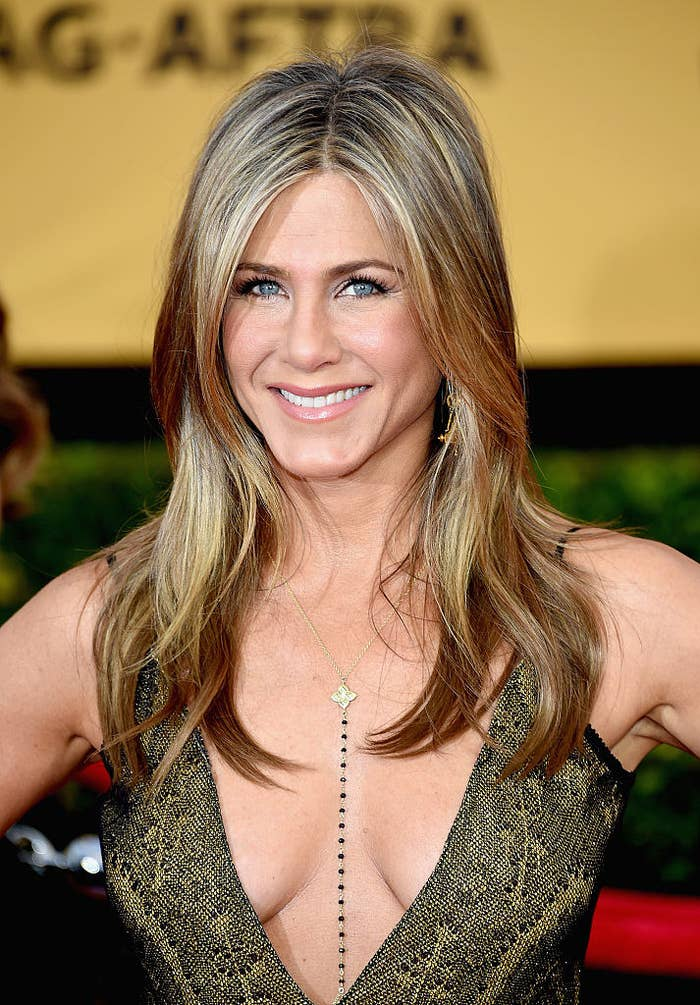 Jennifer Aniston in low-cut dress with hands on hips