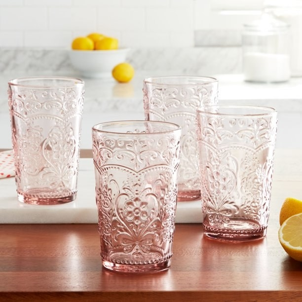 four rose colored glass tumblers on a table