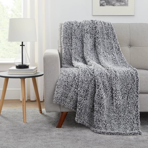 grey sherpa blanket draped on a couch