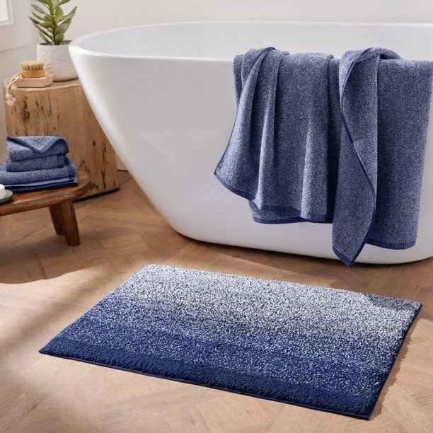 navy blue ombre bath rug next to a bathtub