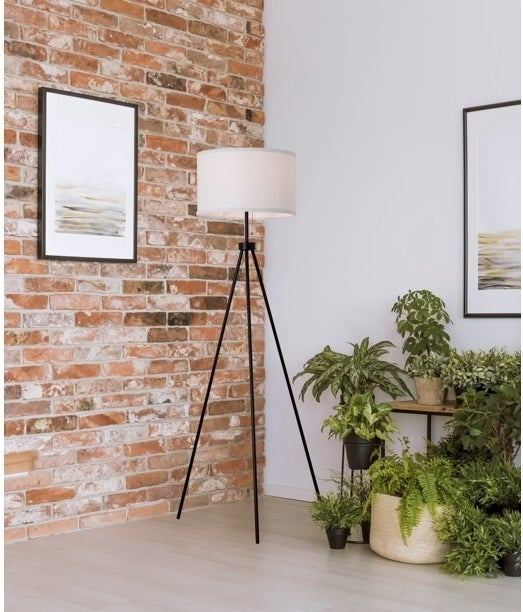 tripod floor lamp with black base and white lamp shade