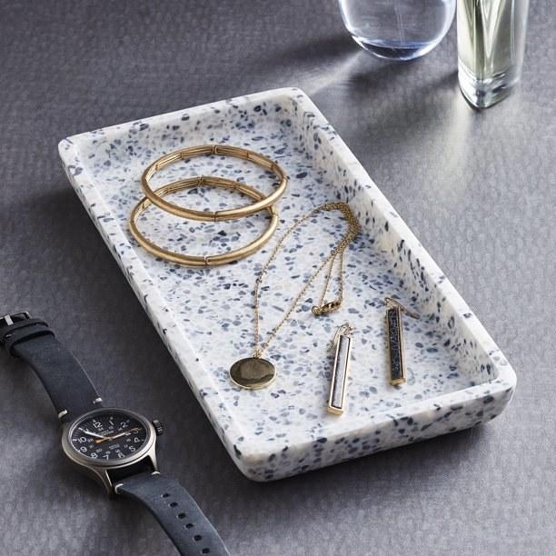 rectangular terrazzo tray with jewelry in it