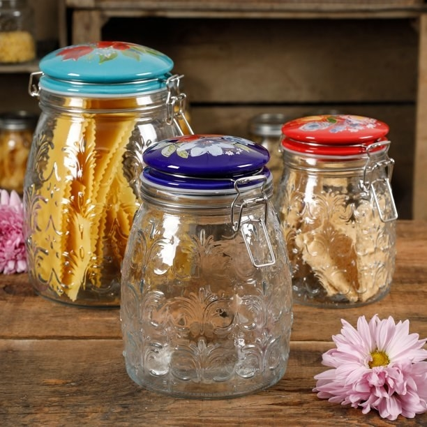 three glass clamp jars with flower patterned ceramic lids