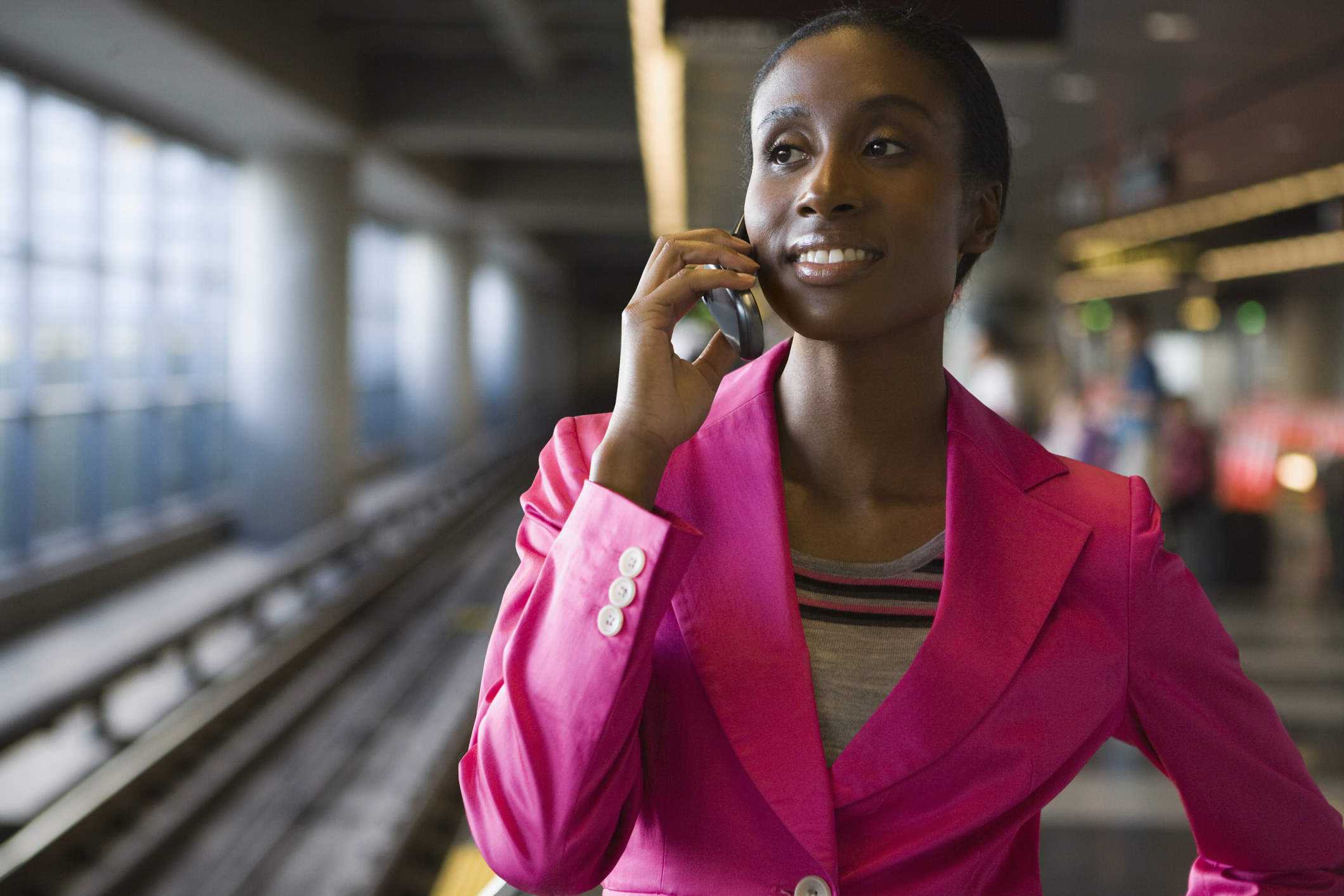 Woman in pink suit on phone while standing on subway platform