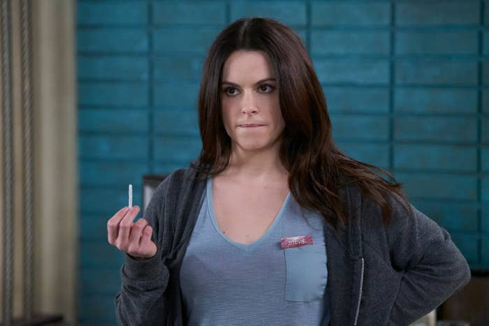 Emily Hampshire holds a thin white item between her fingsers