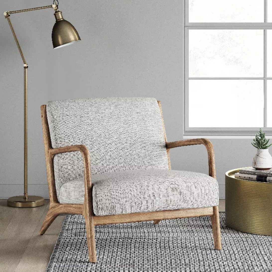 a grey upholstered armchair with light wood arms and legs, sitting in a corner