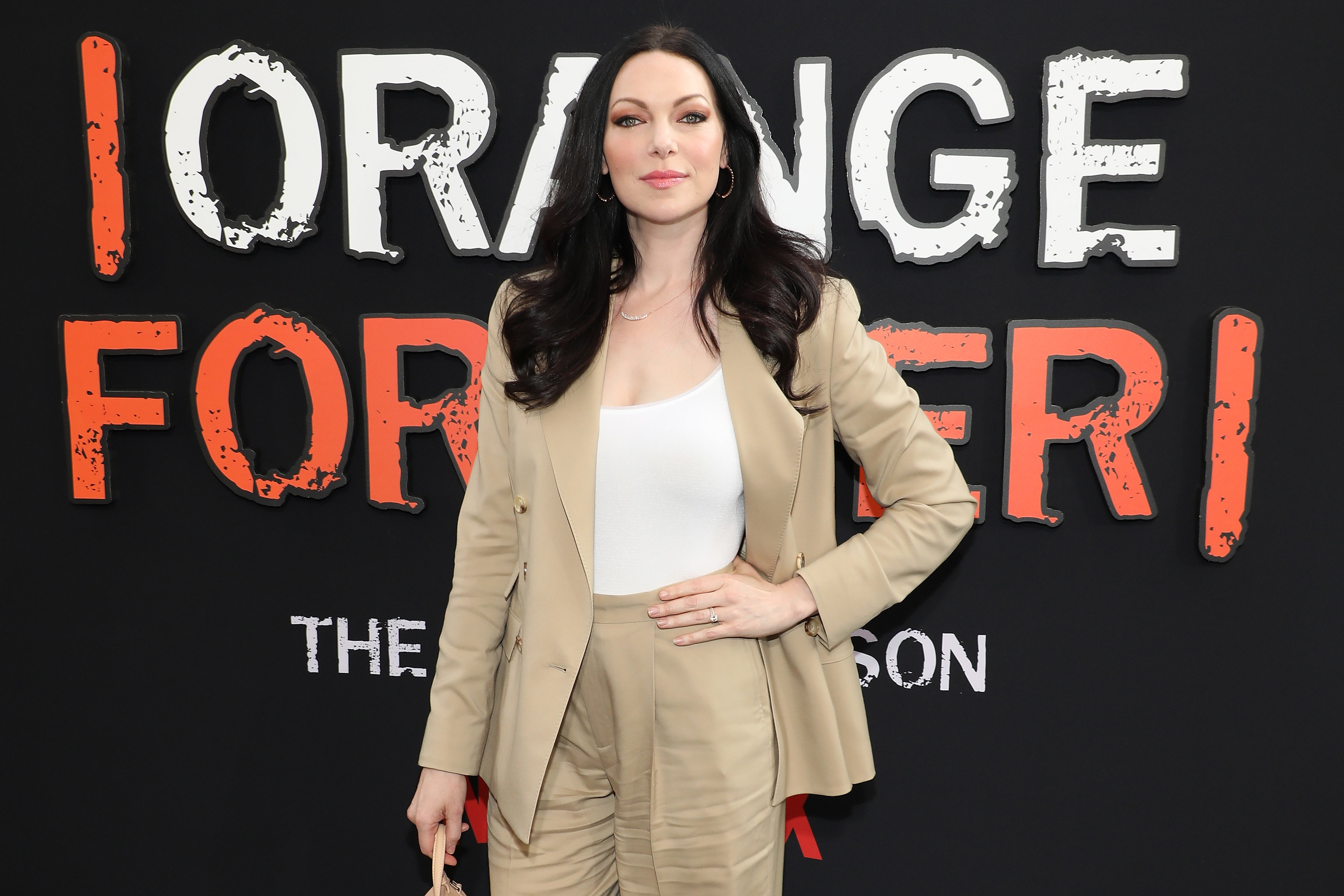 Laura at a Orange Is the New Black event with her hand on her hip