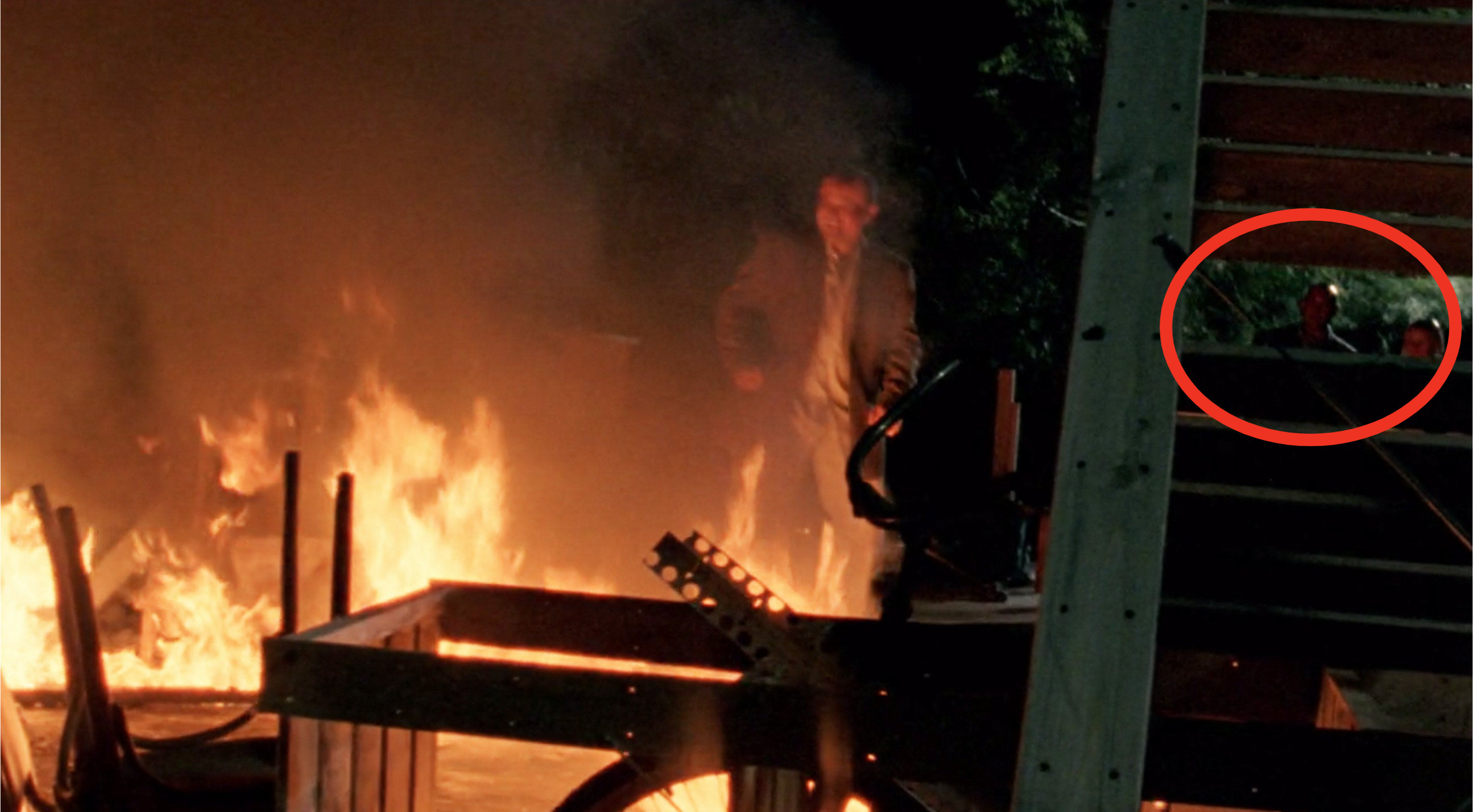 Keith standing behind a huge fire and crew members visible in the background