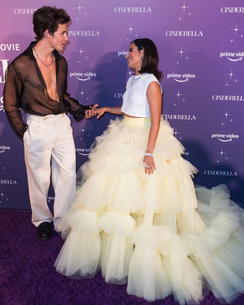 Shawn and Camila hold hands and look at each other on the red carpet