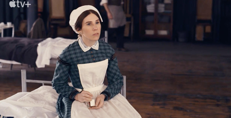 Zosia Mamet as Louisa May Alcott sits