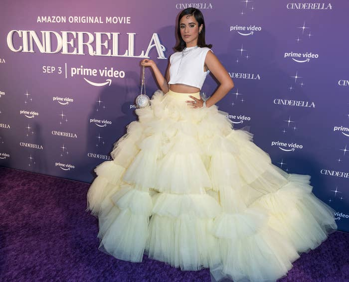 Camila, hand on hip and holding a small disco ball clutch in the other, wearing a long, wide tulle skirt