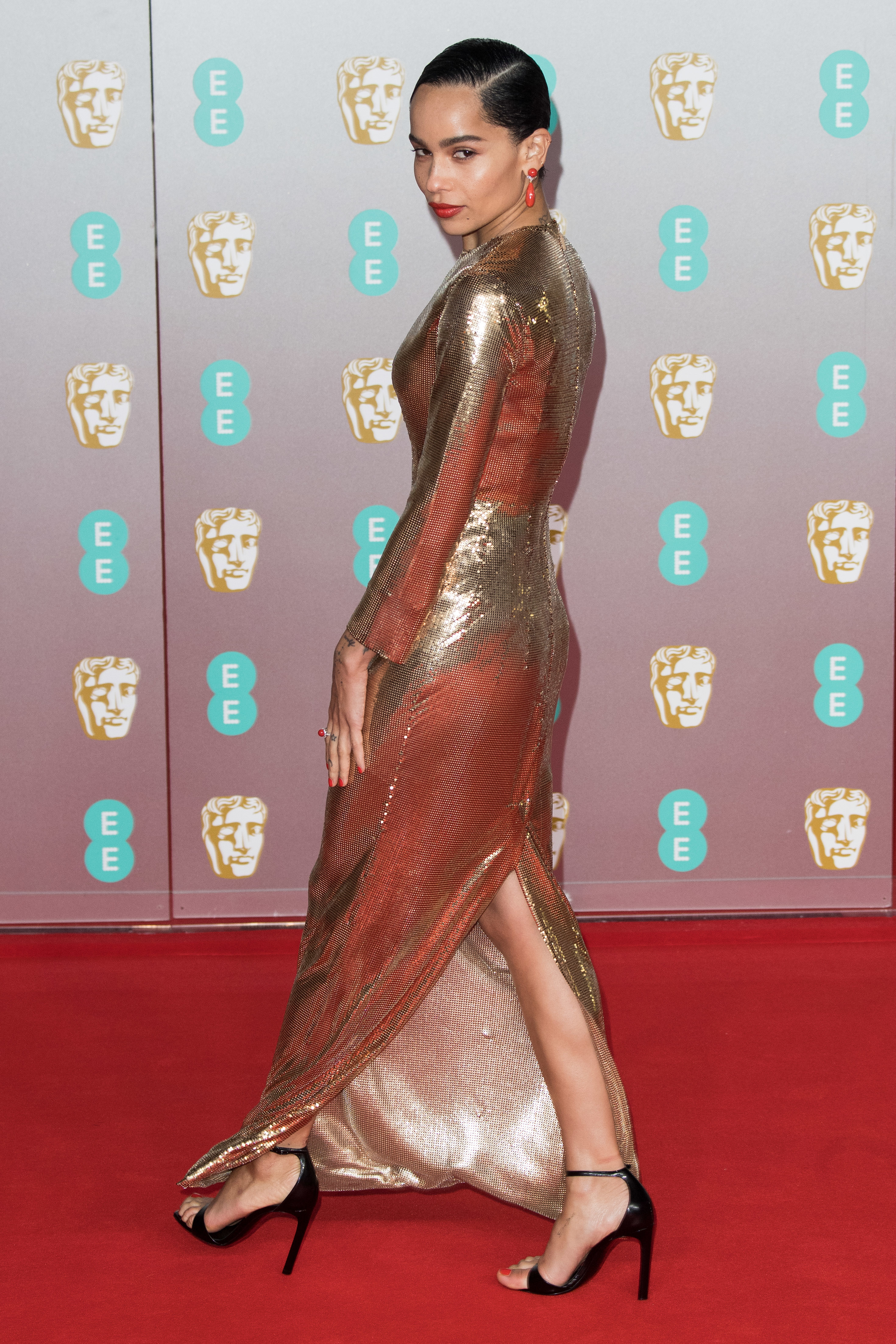 Zoe on red carpet in long metallic gown with high heels